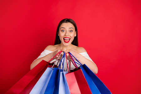 Close up photo of impressed lady holding bright bags screaming shouting wearing white top isolated over red background Stockfoto
