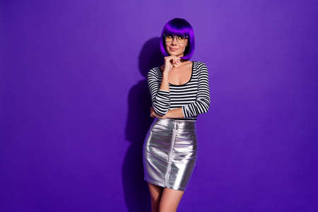 Photo of pretty lady look empty space tricky mood wear specs glossy skirt wig striped pullover isolated purple background 版權商用圖片