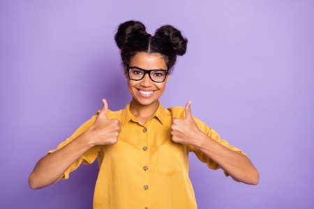 Photo d'une femme à la peau assez foncée et étonnante tenant le pouce vers le haut levé exprimant son accord de bonne qualité porter des spécifications chemise jaune fond de couleur violet isolé