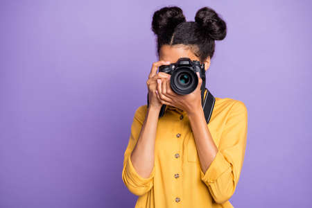 Photo of amazing dark skin lady holding photo digicam in hands photographing, foreign sightseeing abroad wear yellow shirt trousers isolated purple color background