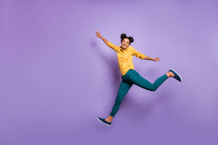 Full body profile photo of pretty dark skin lady jumping high hurrying sale shopping black friday season wear casual yellow shirt trousers isolated purple color background