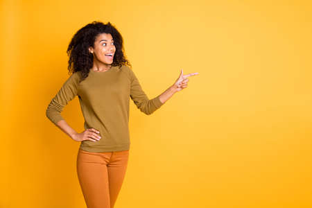 Photo of pretty dark skin salesperson lady indicating finger side empty space proposing sale shopping prices wear casual pullover pants isolated yellow color background