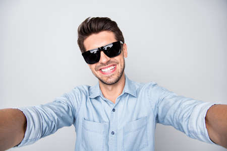 Photo of white cheerful attractive handsome man taking selfie showing his teeth in smile wearing spectacles isolated over grey color background