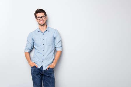 Photo d'un homme intelligent positif et joyeux, souriant à pleines dents, tenant les mains dans les poches isolées sur fond de couleur grise Banque d'images