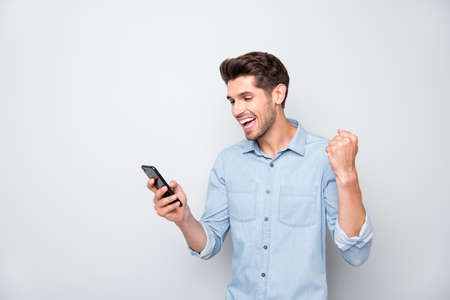 Yeah new like. Turned photo of crazy man at copyspace use cellphone got message read news raise fists feel lucky win social network lottery wear style denim jeans shirt isolated grey color background