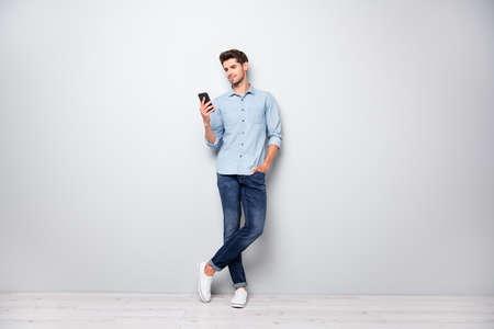 Foto in voller Größe von konzentriertem SMM-Arbeiter, der Handy-Antwort-SMS-Nachrichten verwendet, Online-Konversation mit Freunden hat, Kommentare eingeben, stylische Outfit-Turnschuhe tragen, isoliert grauer Hintergrund color Standard-Bild