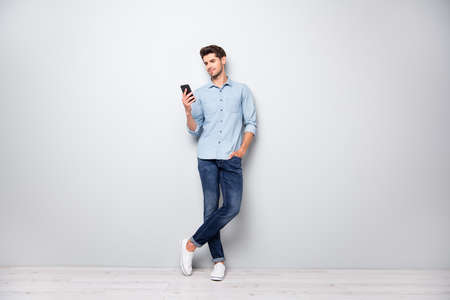 Foto op volledige grootte van geconcentreerde smm-werknemer man gebruik mobiel antwoord sms-berichten online gesprek met vrienden typen opmerkingen berichten dragen stijlvolle outfit sneakers geïsoleerde grijze kleur achtergrond Stockfoto