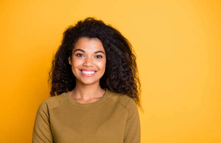 Closeup photo of amazing pretty dark skin lady toothy beaming smiling adorable wavy hairstyle wear casual pullover isolated on yellow color background Фото со стока