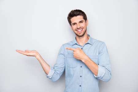 Portrait of positive cheerful promoter man hold hand point index finger indicate information about promotions sales discount suggest feedback wear casual style outfit isolated grey color background