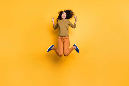 Full length body size photo of cheerful excited ecstatic positive cute curly wavy girlfriend rejoicing about having won competitions wearing orange pants trousers isolated over vivid color background