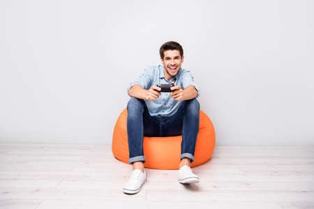 Full length body size photo of trendy man addicted to playing video games wearing white sneakers holding joy stick with hands isolated over grey color background