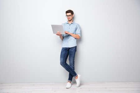 Photo pleine longueur de la taille du corps d'un gestionnaire de coworking intelligent et sérieux, debout en toute confiance, les jambes croisées, à la recherche de nouvelles via une connexion Internet, fond de couleur gris isolé Banque d'images