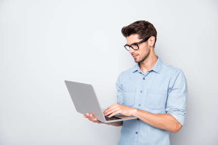 Photo of thoughtful focused clever interested freelancer holding laptop with hands wearing eyeglasses working on deadline project isolated grey color background 写真素材
