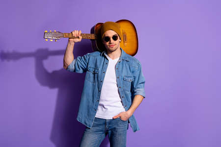 Photo of confident attractive handsome man wearing brown cap spectacles standing with guitar on his shoulder and hand in pocket isolated over purple vibrant color background