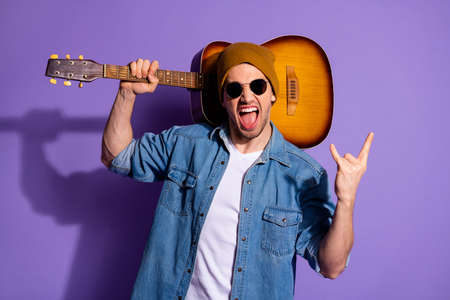 Photo of cheerful attractive rocker screaming trendy showing you rock sign fingers horned holding acoustic guitar in shoulder wearing denim spectacles isolated purple vivid color background