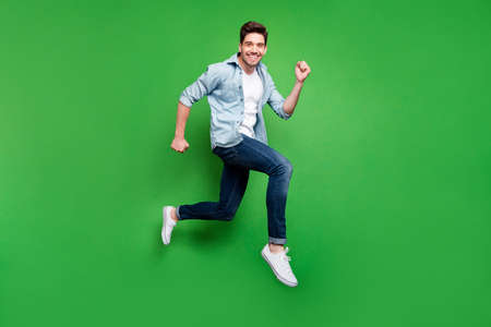 Full body profile photo of handsome guy jumping high sportive competition participant running fast wear casual denim clothes isolated green color background