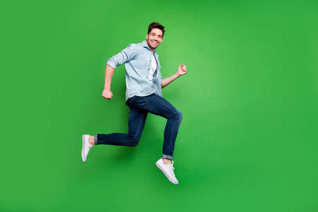Full length body size photo side profile of running jumping ecstatic man wearing white sneakers smiling toothily urgent for sales at shopping center isolated over vivid green color background