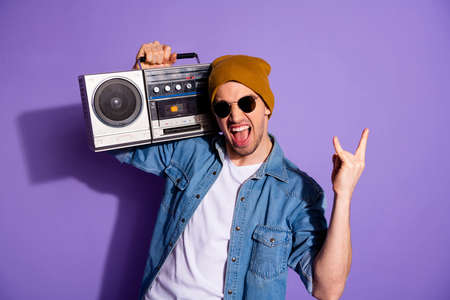 Photo of trendy stylish white screaming man holding retro recorder with hands showing you rock sign shouting wearing denim t-shirt cap headwear isolated purple bright color background