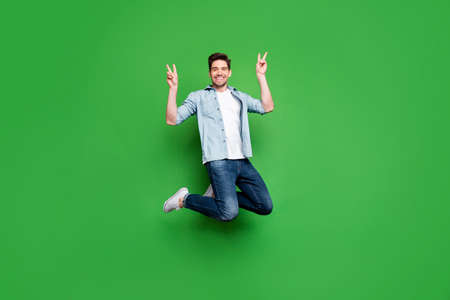 Full length body size photo of kind friendly cheerful man showing you double v-sign greeting you isolated over green vivid color background while jumping up