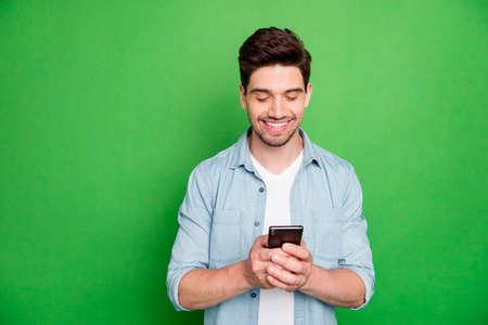 Foto von fröhlichem, positivem, modernem Kerl, der sein Telefon durchsucht und nach Informationen sucht, die auf grünem, lebendigem Hintergrund isoliert sind