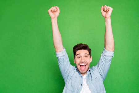 Photo of amazing crazy guy yelling loudly celebrating favorite football team victory raise fists up wear casual denim shirt isolated green color background