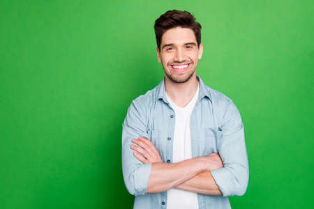 Photo of amazing business guy in excited mood with crossed hands looking forward to start working day wear casual denim shirt isolated over green color background