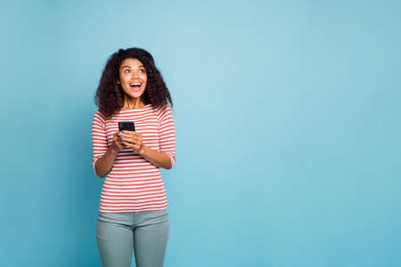 Photo of cheerful charming cute nice curly wavy black woman holding telephone rejoicing with feedback being got wearing striped t-shirt trousers pants looking into empty space isolated blue pastel color background