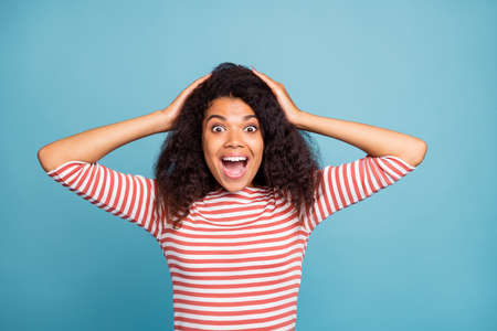 Photo of pretty dark skin lady with open mouth holding hands on head not believe really low shopping prices wear casual striped sweater isolated pastel blue color background