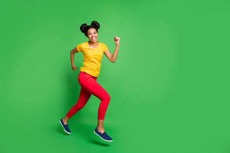 Full size profile photo of pretty dark skin lady jumping high sports competition jogging participant wear casual yellow t-shirt red pants isolated green background