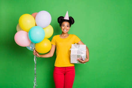 Photo of pretty dark skin lady holding many air balloons and big giftbox came to birthday party wear casual yellow t-shirt red trousers paper cap isolated green background