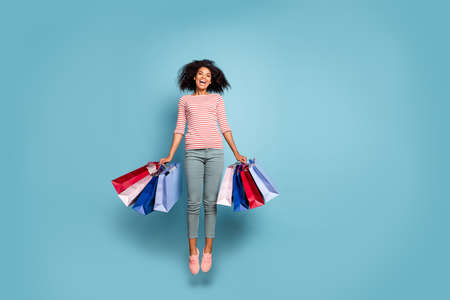 Full length body size photo of stretching jumping excited crazy rejoicing girl black friday packages in striped t-shirt trousers pants footwear isolated over blue pastel color background