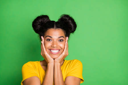 Closeup photo of pretty dark skin lady holding arms on cheeks having best weekend mood toothy smiling wear casual yellow t-shirt isolated green background