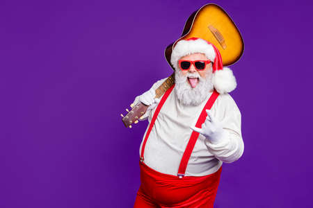 Portrait of his he nice naughty cheery glad cheerful cool bearded thick fat Santa carrying guitar showing horn sign having fun isolated over bright vivid shine vibrant violet lilac background