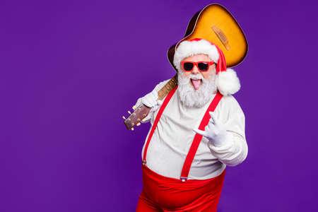Ritratto del suo lui simpatico giocherellona allegro lieto allegro fresco barbuto grasso grosso Babbo Natale che porta la chitarra che mostra il segno del corno divertendosi isolato sopra brillante vivido splendore vibrante viola sfondo lilla