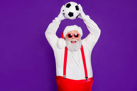 Photo of grey haired santa father holding football ball spend newyear night watching champion league excited final game wear sun specs costume isolated purple background