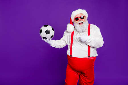 Photo of grey haired santa holding football ball demonstrating new leather model of football ball for discount x-mas price wear sun specs costume isolated purple background