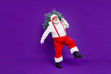 Let it snow. Full length photo of funny fat santa father holding x-mas tree on shoulder wanna make perfect eve wear sun specs costume isolated purple background