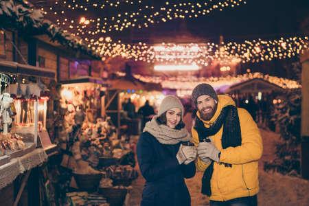 Photo de deux personnes en couple avec une boisson au thé chaud dans les mains célébrant la nuit de la veille de Noël passer du temps magique à l'extérieur atmosphère du nouvel an shopping marché porter des vestes Banque d'images
