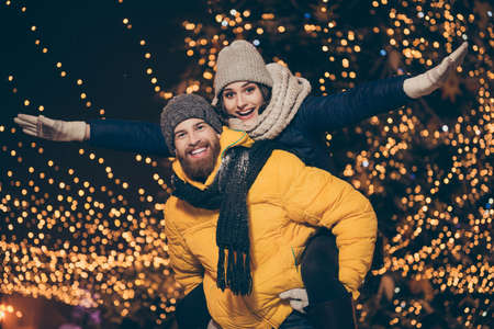 Photo of two people guy lady walking lights night park newyear evening holding piggyback pretending wings flight plane wear winter coats scarfs hats outdoors