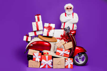 Photo of fat santa man with many newyear giftboxes on bike congratulating children advising parents low prices wear sun specs x-mas costume isolated purple background 免版税图像