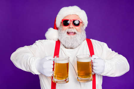 Close-up portrait of nice glad cheerful cheery positive bearded Santa holding in hands two mugs drinking beer having fun isolated over bright vivid shine vibrant violet lilac background 免版税图像