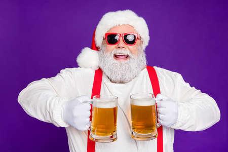 Retrato de primer plano de agradable alegre alegre alegre positivo barbudo Santa sosteniendo en las manos dos tazas bebiendo cerveza divirtiéndose aislado sobre fondo lila violeta vibrante brillante vivo
