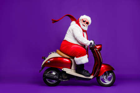 Photo of fat santa claus role man rushing newyear x-mas theme party by bike cool modern style wear sun spectacles trousers hat suspenders isolated purple background 写真素材
