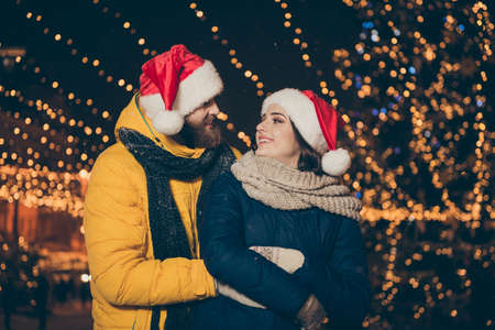 Photo of two people guy lady emotionally look eyes park newyear evening frosty weather stand piggyback having fun wear winter coats scarfs santa hats gloves outside