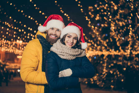 Photo of two people guy lady visit city central park x-mas evening frosty weather stand piggyback outdoors party wear winter jackets scarfs santa hats gloves outside