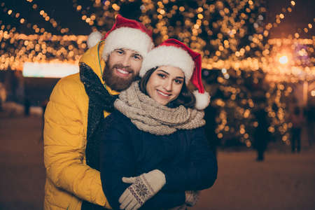 Merry christmas. Photo of two people guy lady visit city illuminated park x-mas evening frosty weather stand piggyback wear winter jackets scarfs santa hats outdoors
