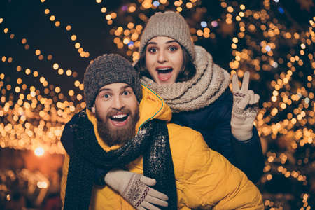 Photo of two people playing illuminated night park x-mas eve husband guy carry piggyback wife lady showing v-sign symbol wear winter jackets scarfs hats outdoors