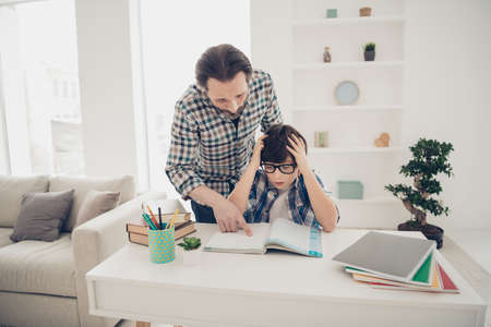 I do not know how to do learn foreign language concept. Patient clever intelligent daddy helping his confused scared son with preparing for exam test