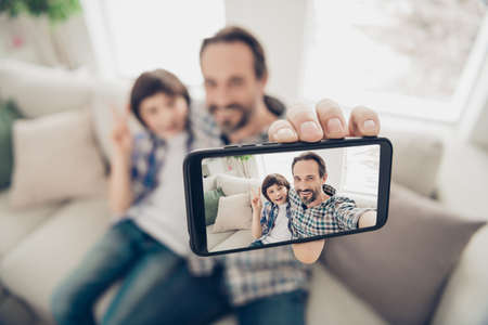 Phto portrait of handsome positive cheerful dad hugging embracing his son on couch taking selfie on telephone showing v-sign having best weekend sitting in living room indoors