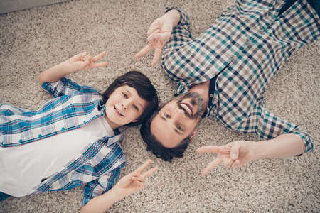 High angle above close up view photo of excited crazy handsome nice glad optimistic guy and his small student son making v-sign symbol to you lying on white soft fluffy carpet living room on weekend